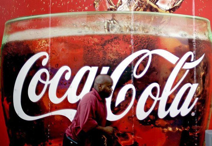 Un hombre pasa junto a una valla publicitaria de Coca -Cola fuera de una tienda de conveniencia en Atlanta. Coca -Cola dijo que está cortando los puestos de trabajo en todo el mundo. (Agencias)