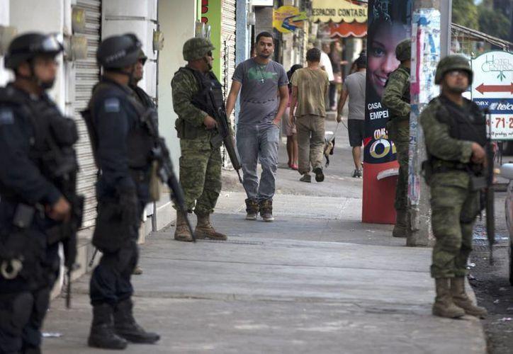 Policías federales y soldados vigilan una calle en Apatzingán, Michoacán, este miércoles. (Agencias)