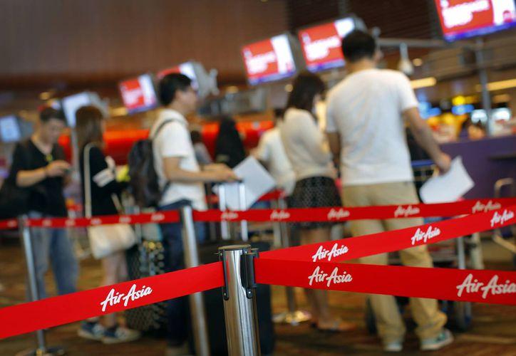 Pasajeros hacen cola para facturar en sus vuelos de AirAsia ante los mostradores de la aerolínea en el aeropuerto internacional de Changi, Singapur. (Foto AP/Wong Maye-E)