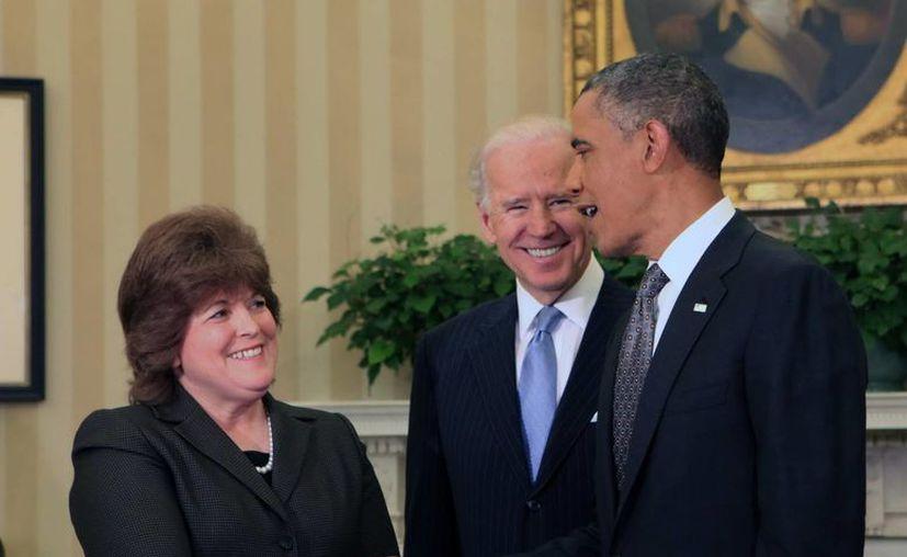 El presidente Obama saluda a Julia Pierson ante la mirada del vicepresidente Joe Biden, tras la toma de juramento de Pierson como nueva directora del Servicio Secreto. (EFE)