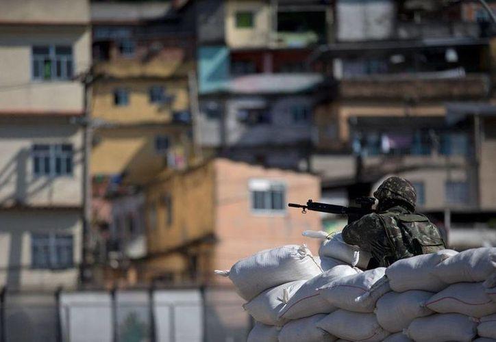 Soldado prueba la mira de su rifle, cerca de una favela de Río de Janeiro, Brasil. Este domingo, durante las elecciones presidenciales, las fuerzas de seguridad reforzarán la vigilancia en los lugares más violentos del país. (AP)