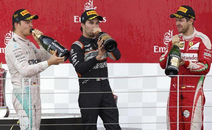De i a d: el piloto alemán de Mercedes, Nico Rosberg; el mexicano de Force India, Sergio Perez, y Sebastian Vettel, alemán de la escudería Ferrari. (AP)