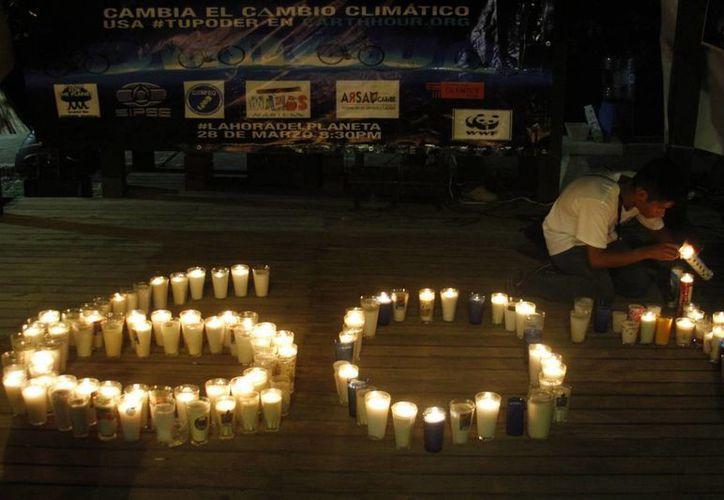 Los participantes encendieron las velas que formaron el símbolo. (Israel Leal/SIPSE)