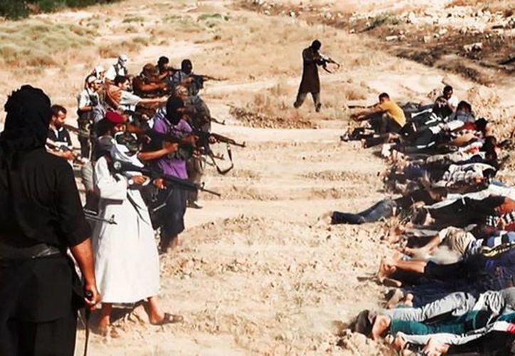 Imagen del 14 de junio de 2014, que muestra a milicianos del Estado Islámico apuntando a soldados irquíes con ropa de civil, capturados en una base en Tikrit, Irak. (Archivo, tomada de AP de una web de un sitio de milicianos)