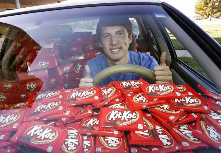Fotografía del Hunter Jobbins, estudiante de la Universidad Kansas State, mientras posa en su automóvil con casi 6.500 barras de chocolate Kit Kat en Manhattan, Kansas. (Colin E. Braley/AP Images for The Hershey Company)