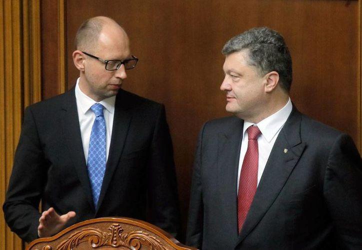 El Parlamento desechó hoy la renuncia del primer ministro de Ucrania, Arseni Yatseniuk (izq.), quien deberá permanecer en su cargo. En tanto, el presidente Petro Poroshenko (der.), urgió a los legisladores a llegar a un acuerdo. (AP)