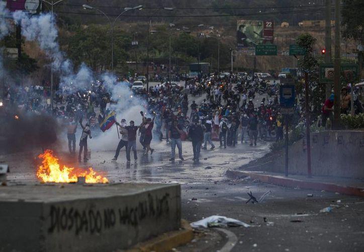 Un grupo de manifestantes opositores al gobierno de Nicolás Maduro participa en una manifestación y se enfrenta a miembros de la Policía Nacional Bolivariana. (Archivo/EFE)