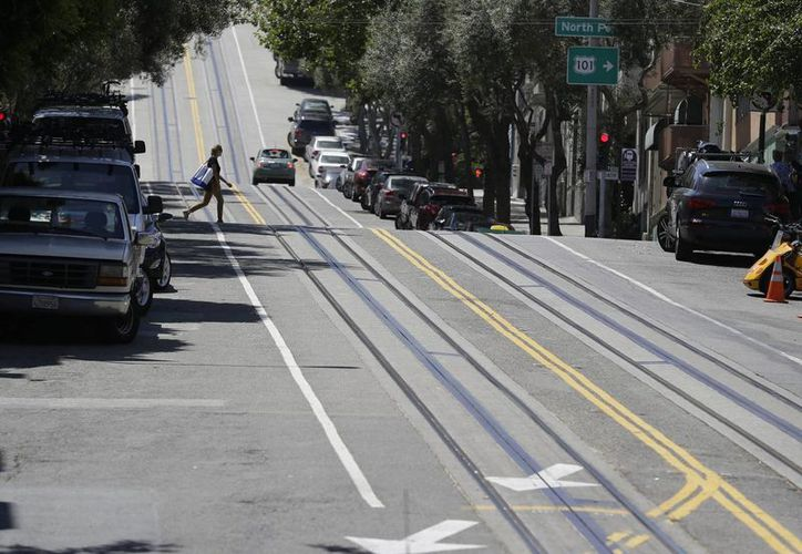 Una mujer cruza Hyde Street y los rieles vacíos de tranvías. (Agencias)