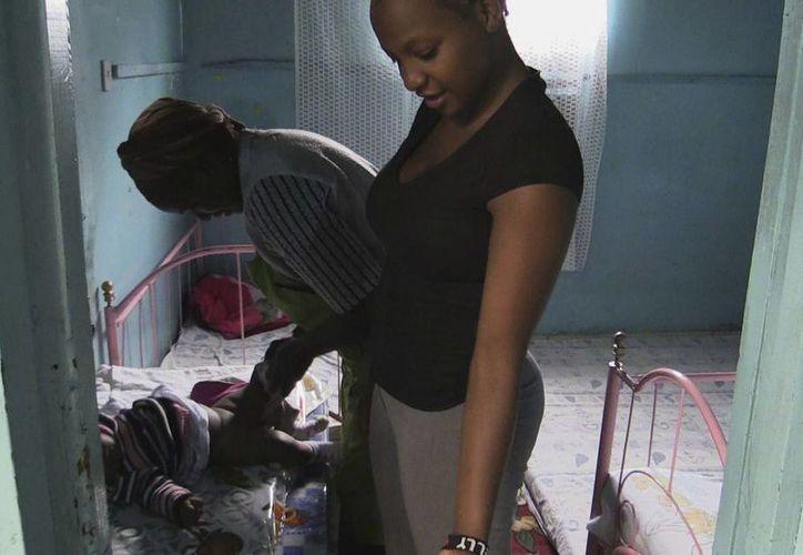 Dos cuidadoras cambian el pañal a Quentin, el bebé más pequeño de una guardería del barrio chabolista de Dandora, en Nairobi. (EFE)