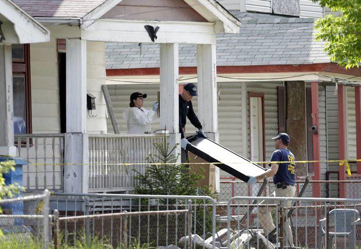 Agentes de la ley retiran evidencias de la casa donde estuvieron cautivas las mujeres, en Cleveland, Ohio. (Agencias)