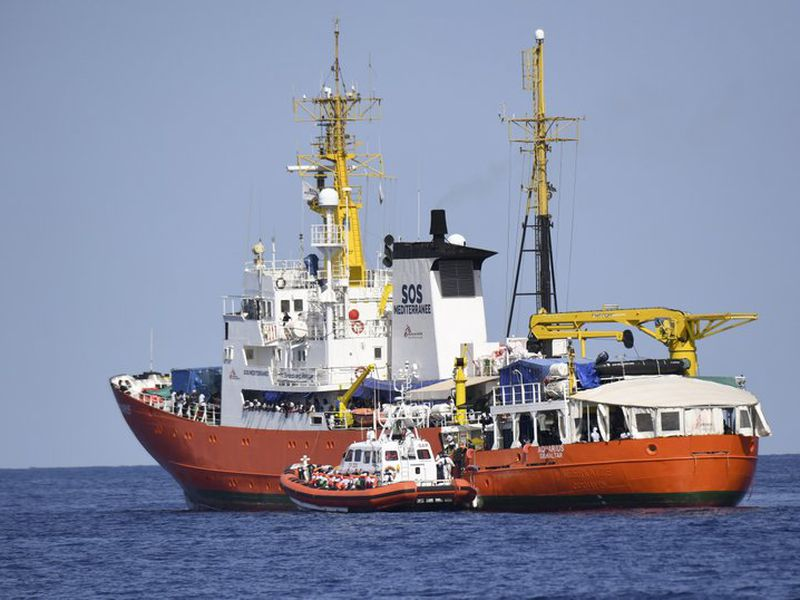 "An Italian Coast Guard boat approaches the French NGO ""SOS Mediterranee"" Aquarius ship as migrants are being transferred, in the Mediterranean Sea. (AP)"