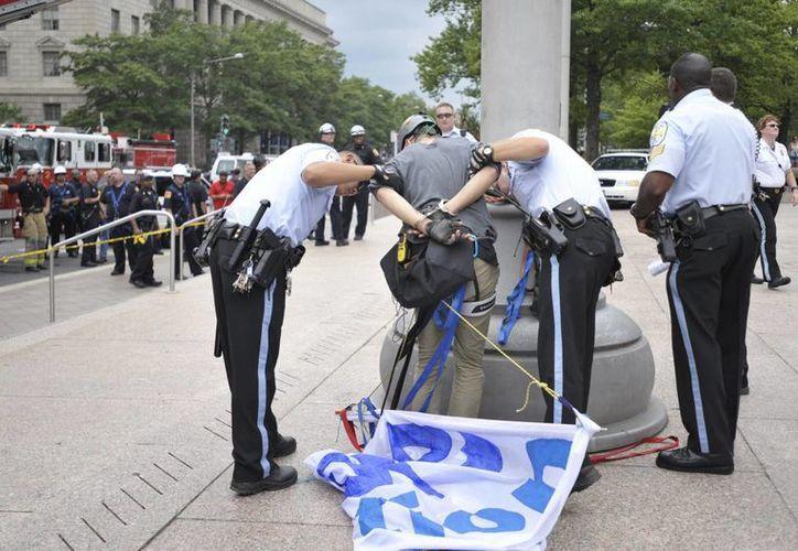 Agentes someten a una persona en Washington, luego que dos activistas pusieron estandartes en astabanderas de la Plaza de la Libertad para exigir el fin de las deportaciones, el pasado 2 de agosto de 2014. (Notimex)