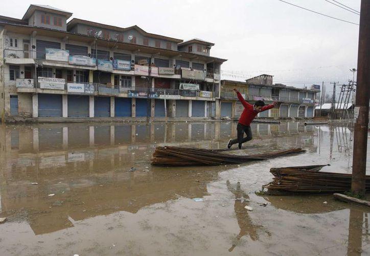 Un hombre salta para cruzar una calle en Pampore, en la India. Al menos 25 muertos se reportaron en el distrito de Purnea. (EFE/Archivo)