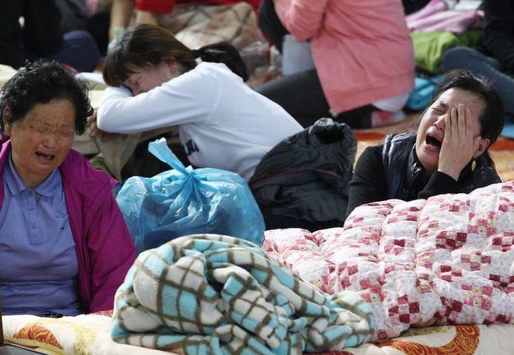Familiares de las víctimas lloran después de enterarse de la muerte de sus parientes. (Agencias)