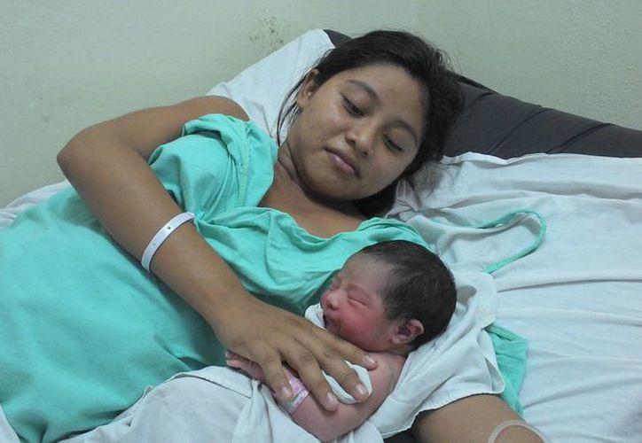 María Máxima Tec Cahuich posando con su hijo, el primer yucateco que nació en 2014 a las 12:42 horas. (Milenio Novedades)