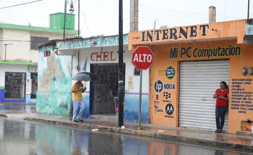 En Felipe Carrillo Puerto se registró una llovizna que obligó a algunos peatones a sacar el paraguas. (Ángel Castilla/SIPSE)