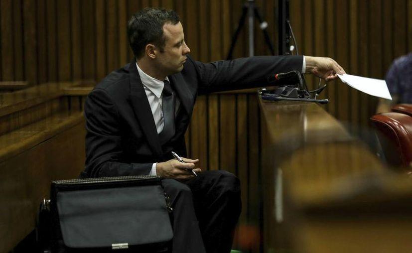 Pistorius pasa una nota a sus abogados desde el banquillo de los acusados durante el juicio en el Tribunal Superior de Justicia en Pretoria. (EFE)