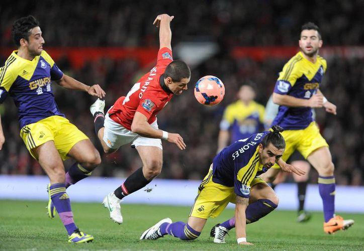 """El delantero del Manchester United Javier Hernandez (C), """"Chicharito"""" en acción con los jugadores del Swansea City Chico (d) y Jordi Amat (I) durante el duelo de la FA cup, tercera ronda, que se ha disputado en Old Trafford, Manchester, Reino Unido. (EFE)"""