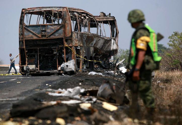 Un soldado custodia el sitio donde quedó el autobús de pasajeros que se incendió tras chocar con un camión cerca de Ciudad Isla en el estado de Veracruz. (AP)