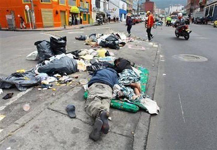 Personas duermen en la acera entre basura no recolectada en una calle de Bogotá. (Agencias)