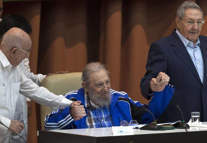 Fidel Castro sostiene las manos de su hermano, el presidente cubano Raúl Castro (a la derecha), y del segundo secretario del Comité Central, José Ramón Machado Ventura, momentos antes del himno del partido comunista durante la ceremonia de clausura del congreso de esa fuerza en La Habana, Cuba. (Agencias)