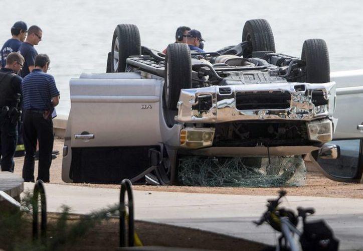 Las autoridades trabajan en la escena de un accidente en el que un vehículo cayó a un lago en Tempe, Arizona, con cinco ocupantes. (Agencias)
