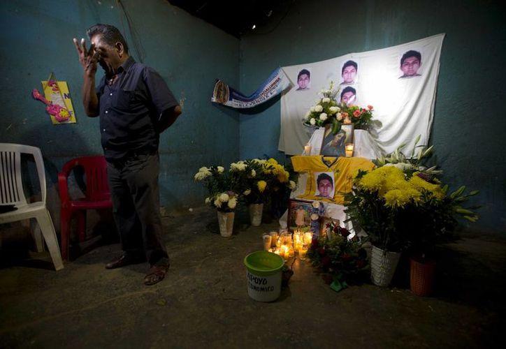 Ezequiel Mora junto a la ofrenda en honor a su hijo Alexander, de 19 años, único de los 43 normalistas desaparecidos en Iguala que ya fue identificado. (Foto: AP)