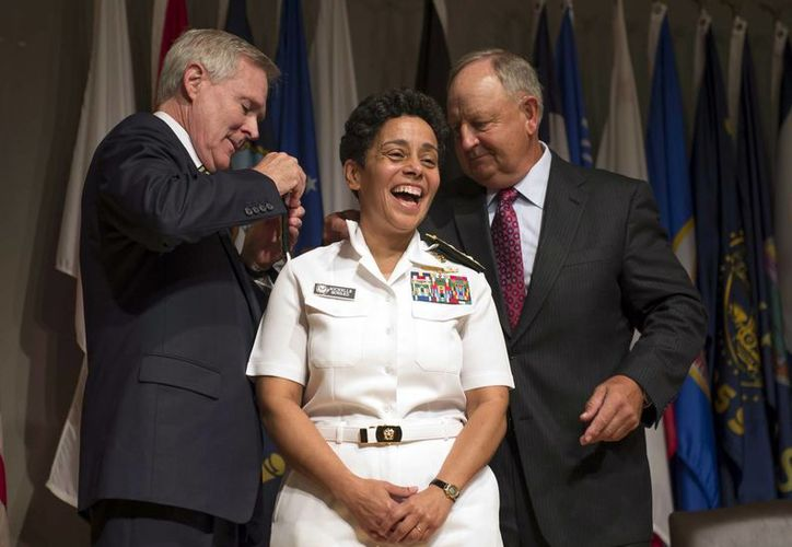 Michelle Janine Howard sonríe mientras el secretario de Marina Ray Mabus (izq) y su esposo Wayne Cowles le colocan las palas de su nueva jerarquía.(Foto: AP: U.S. Navy, Chief Mass Communication Specialist Peter D. Lawlor)