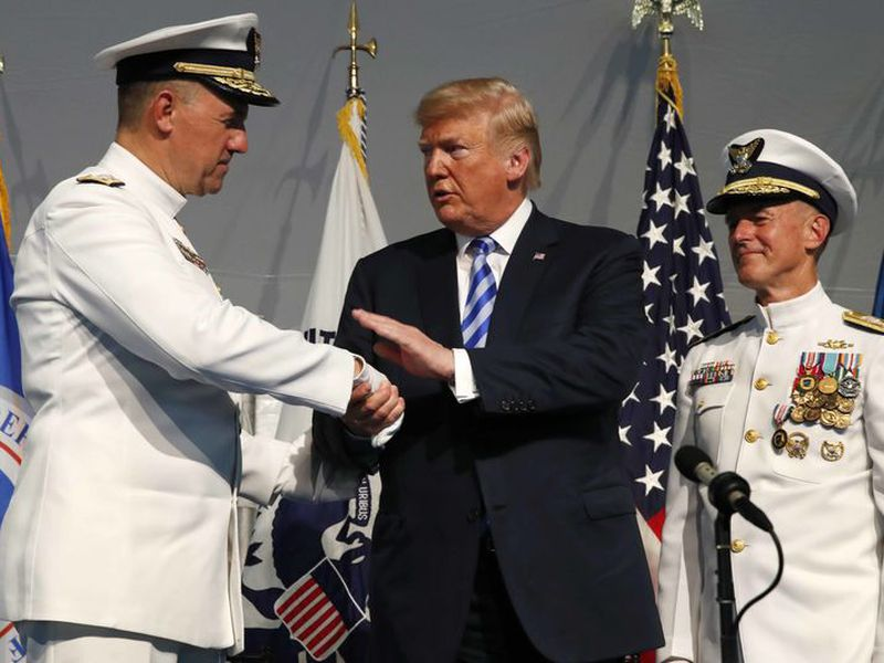President Donald Trump, center, shakes hands with Coast Guard Adm. Karl Schultz, left. Trump says he wouldn't mind seeing the North American Free Trade Agreement replaced by two separate, bilateral trade deals with Canada and Mexico.