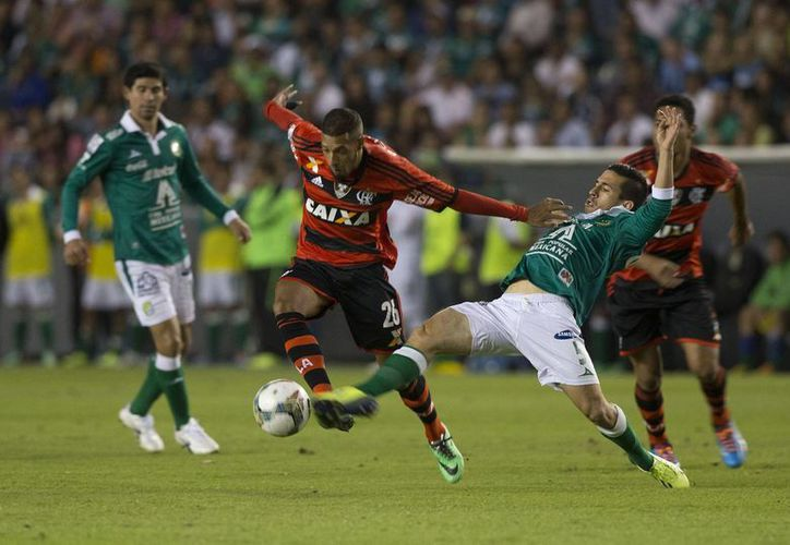 Fernando Navarro (d), del León, disputa el esférico con Paulinho, del Flamengo. (Agencias)