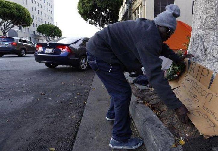 Un indigente coloca un letrero en el lugar donde la policía asesinó al hombre conocido como 'Africa'. (Francine Orr/Los Angeles Times)