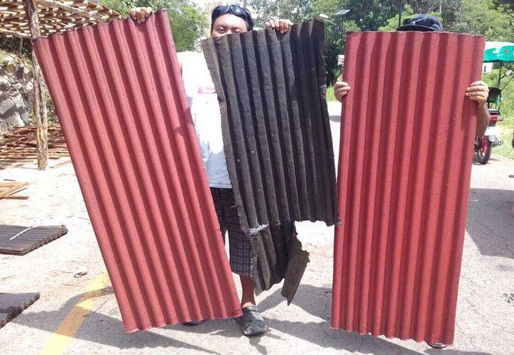 Los operadores muestran las piezas de laminas rotas, viejas y secas que les envió José Baladez Chi para 'ayudarlos'. (Alejandro Poot)
