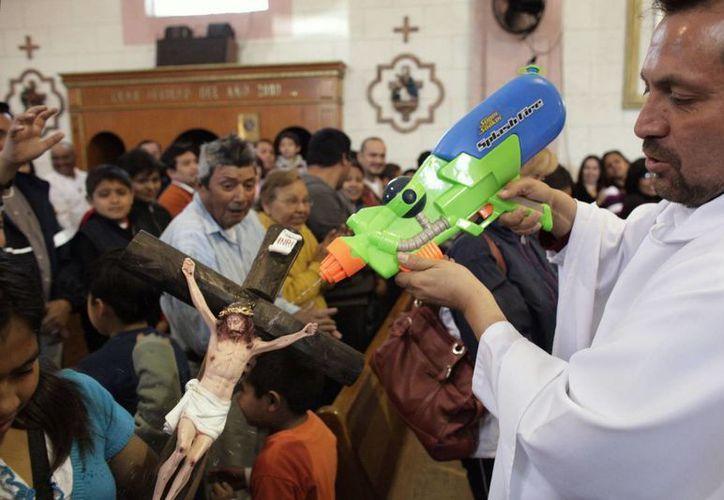 El padre Humberto 'dispara bendiciones' con un arma de juguete que recibió de pequeño. (Archivo/lapatilla.com)