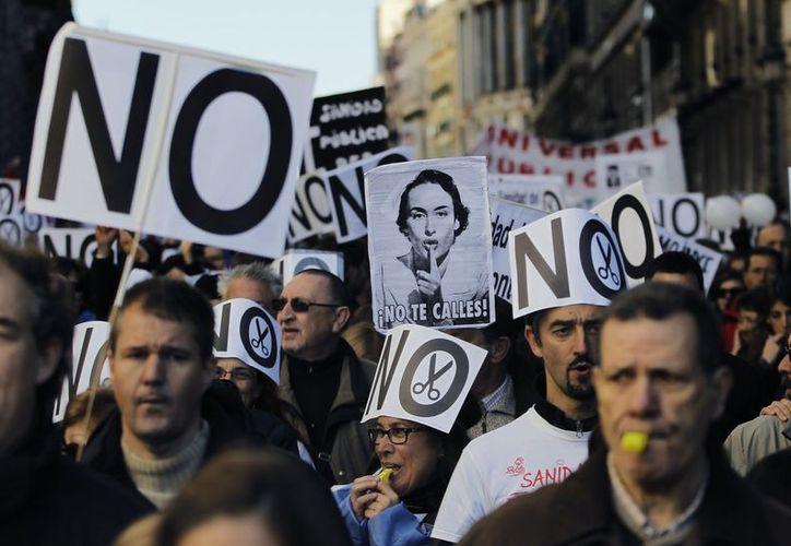 Manifestantes sostienen pancartas y utilizan silbatos en Madrid en contra de las medidas austeras impuestas por el gobierno. (Agencias)