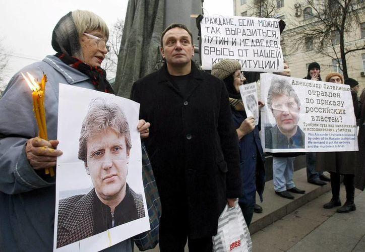 Un grupo de defensores de los derechos humanos y representantes políticos de la oposición muestran fotografías del ex agente del KGB Alexandre Litvinenko asesinado en Londres en 2008. (EFE)