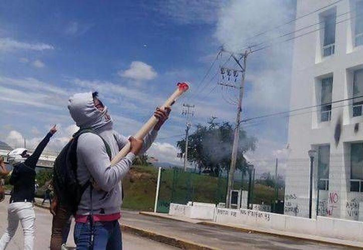 Los estudiantes lanzaron objetos flamables hacia las ventanas de la Ciudad Judicial del municipio de Iguala, Guerrero. (Milenio)