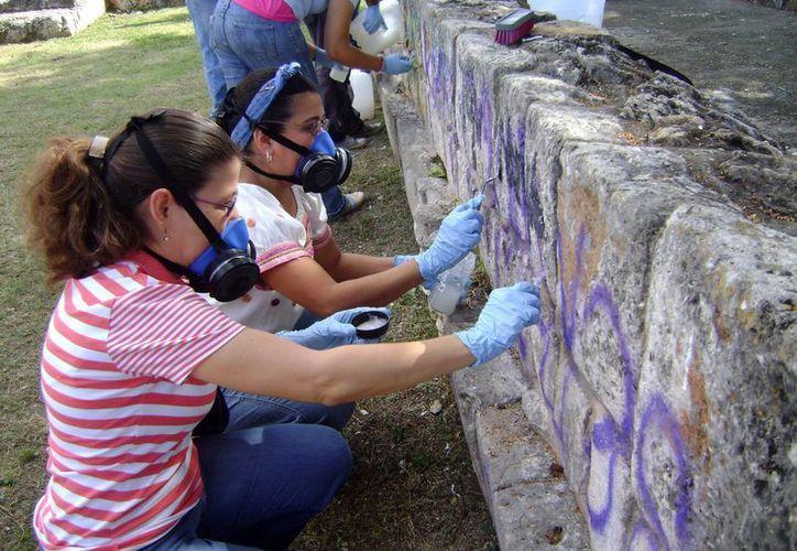 Especialistas en conservación realizan los trabajos de restauración en vestigios arqueológicos que existen en parques de Mérida. (Milenio Novedades)