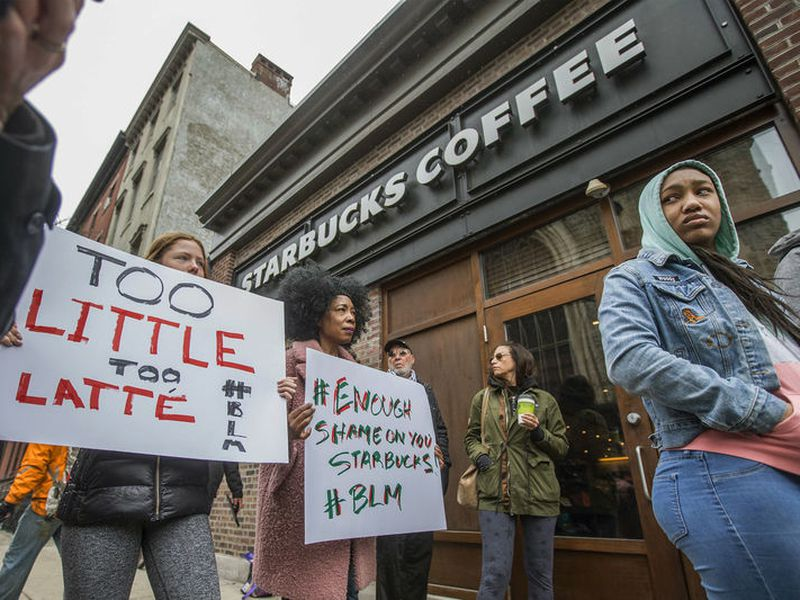 Protesters gather outside of a  Starbucks in Philadelphia, Sunday, where two black men were arrested Thursday after employees called police to say the men were trespassing. The arrest prompted accusations of racism on social media.