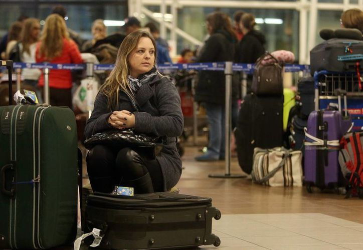 Una mujer espera la salida de sus vuelos este martes en el Aeropuerto Internacional de Santiago de Chile, donde cientos de empleados realizaron un paro de labores para exigir mejores condiciones laborales. (EFE)