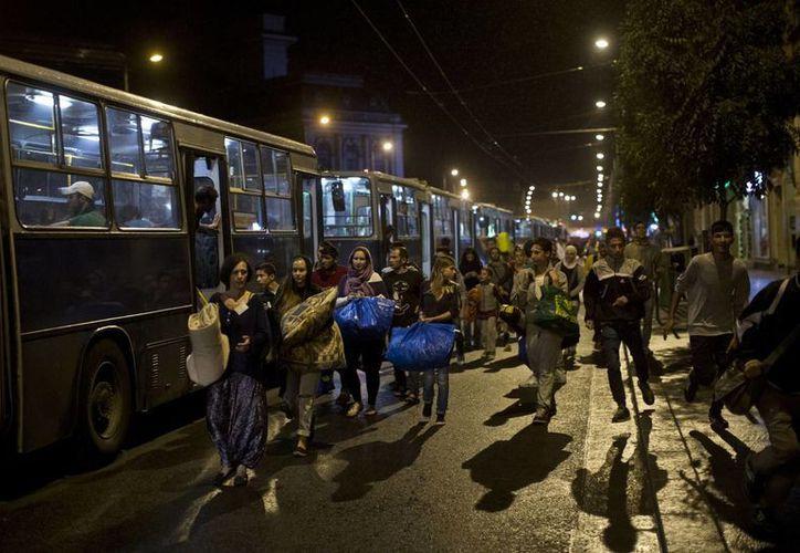 Inmigrantes exhaustos caminan para abordar autobuses proporcionados por autoridades húngaras en la estación de tren de Keleti en Budapest, Hungría, el sábado 5 de septiembre de 2015. (Foto AP/Marko Drobnjakovic)