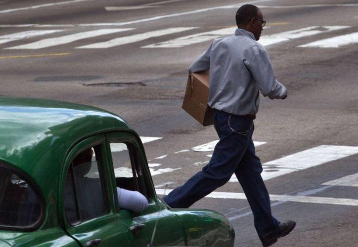 Un hombre cruza la calle frente a un automóvil en marcha en La Habana. (Agencias)