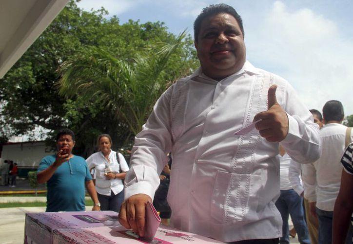Orlando Muñoz deposita su boleta en la urna. (Israel Leal/SIPSE)