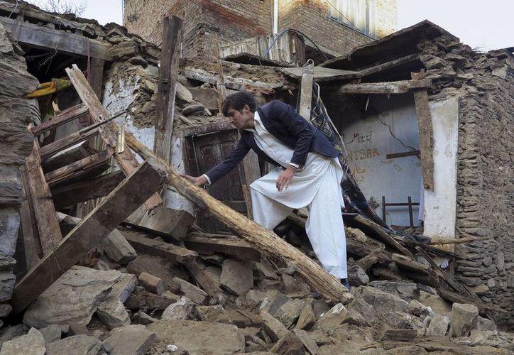 Un hombre paquistaní examina una casa dañada por el terremoto en Mingora, la principal ciudad de Swat Valley. (Agencias)