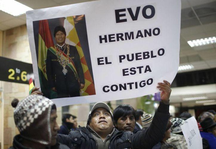 Un hombre sostiene un cartel en apoyo al presidente Evo Morales en el aeropuerto El Alto, Bolivia. (Agencias)