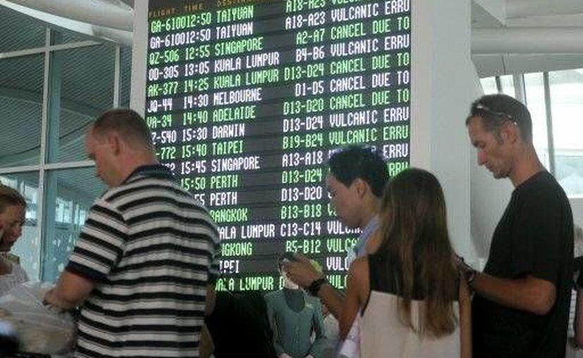 Imagen de los pasajeros que esperan reportes sobre su vuelo en el aeropuerto internacional de Ngurah Rai en Bali, Indonesia. Las terminales aéreas permanecen cerradas por la nula visibilidad por la erupción de 5 volcanes. (Foto AP)