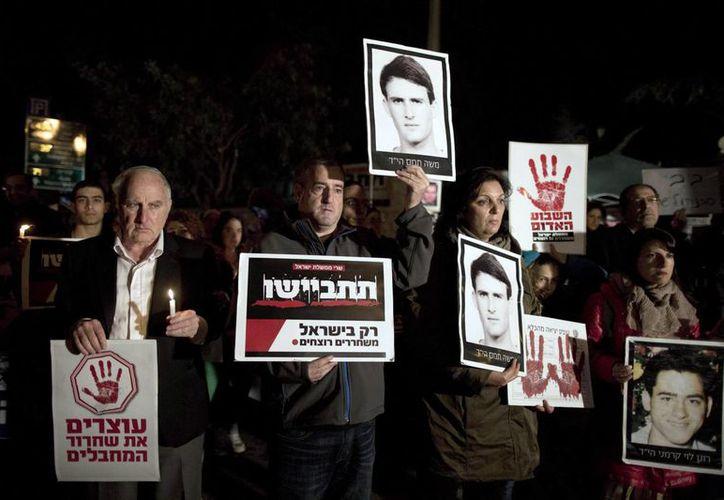 """Familiares de israelíes asesinados por milicianos palestinos sostienen velas y pancartas en hebreo que dicen: """"Alto a la liberación de asesinos"""" y """"Vergüenza: Sólo Israel libera asesinos"""" durante una manifestación frente a la residencia del primer ministro en Jerusalén, Israel. (EFE)"""