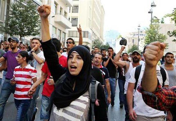 Manifestantes libaneses corean durante una protesta por la actual crisis de basura y la disfunción polític en Beirut, Líbano. (Foto AP/Bilal Hussein)