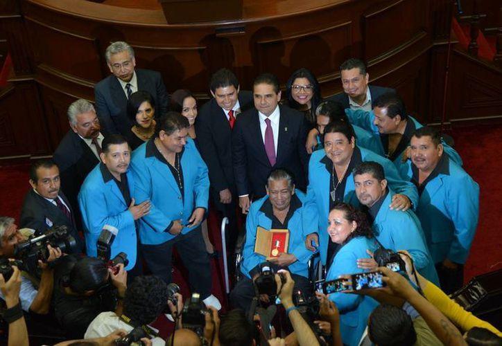 El gobernador de Michoacán, Silvano Aureoles Conejo (c), y un grupo de diputados posan para una fotografía con el grupo musical Hermanos Jiménez y su Arpa, luego de reciben estos últimos una medalla del Congreso Estatal este sábado (EFE)