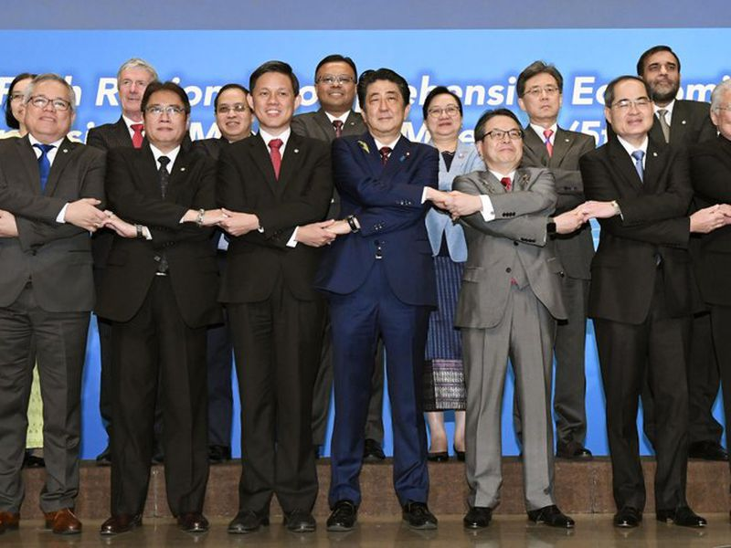 Japanese Prime Minister Shinzo Abe, center, joins hands with trade ministers from Asian countries for a group photo during the Regional Comprehensive Economic Partnership (RCEP) meeting in Tokyo Sunday. (AP)