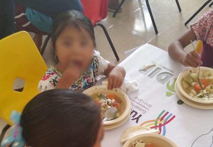 Imagen de unas niñas comiendo durante la inauguración de uno de los comedores comunitarios ubicados en Panabá. (Sergio Grosjean/SIPSE)